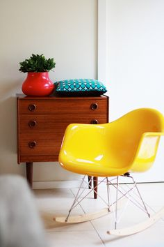 Love the retro vibe and bright colours. Modern, yellow rocking chair, mid-century dresser, orangey vase, turquoise pillow, white background.