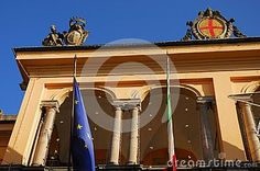 Photo made at the building that is the seat of the municipality of the city of Lodi in Lombardy (Italy). In the picture you see the upper part of the facade of the building consists of a large colonnade. In the foreground there are two flags of the Italian and the European community.Over the roof, having as background the intense blue of the sky, we see a large coat of arms and a statue with an emblem smaller.