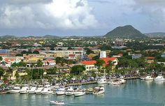 Hooiberg, a volcanic formation, rises behind the island of Aruba's capital, Oranjestad, only a few miles from the coast of Venezuela. Aruba is a tourist haven around the downtown district. Its Dutch-style buildings create a unique atmosphere,  unmistakably the Caribbean. Beaches, water sports, resorts and casinos dominate the landscape. The climate is drier here than elsewhere in the region, so the interior is a desert-like landscape. Four-wheeler and jeep tours and horseback rides are…