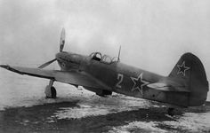 "Soviet Yak-9 with tail number ""2"" at the airport"