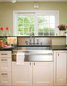 stainless farmhouse sink. white cabinetry. love the towel bar.