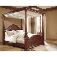 Enjoy the traditional style the Martanny canopy bed brings your bedroom. Featuring cream colored drapes and a warm brown finish that helps complement the room.