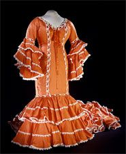 Cuban Rumba Dress    This is a Bata Cubana, or Cuban Rumba dress, donated to the Smithsonian by Celia Cruz, the great Cuban salsa singer, in 1997. The Bata Cubana is a garment worn for performance on stage or cabaret.    The Bata Cubana has its roots in the 19th century, and brings together influences from Spanish, French, and African culture and dress, combining theater, fiesta, and the spectacle of carnival with slave and gypsy dress.
