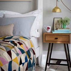 Bedroom interior.  Geometric quilt cover, pendant light, floorboards, side table