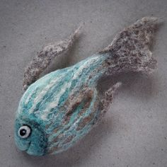 Fish brooch, unique piece of jewellery. Needle felting and wet felting techniques have been combined to create this little fish. It is made of pure animal wool and bamboo fibre: white, beige, brown, blue, black.  Size: approximately 3.75x21.75 inches (10x4.5cm)   I POST ALL MY ITEMS BY SIGNED/TRACKED DELIVERY.  PLEASE READ THE POLICY INFORMATION BEFORE PURCHASING. MY CREATIONS ARE NOT TOYS, PLEASE KEEP OUT OF THE REACH OF CHILDREN. FOR USE AS A DECORATION/JEWELLERY ONLY.  Thank you for…