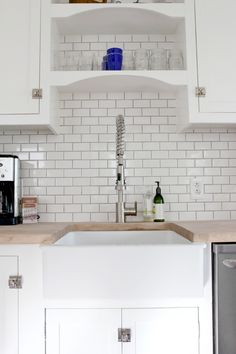 the Grit and Polish - kitchen renovation with apron front sink and industrial faucet. butchers block counters