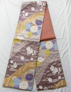 "This is an elegant Fukuro obi with four seasons flowers such as 'Kiku'(chrysanthemum), 'Tsubaki'(camellia) and ""Sakura""(cherry blossom) pattern, which is woven."