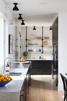 kitchen with black Shaker style cabinets highlighted by Carrera countertops and white subway tiles