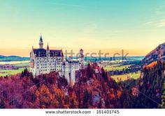 Neuschwanstein, Lovely Vintage Blue Yellow Autumn Landscape Panorama Picture of the fairy tale castle near Munich in Bavaria, Germany with colorful trees in the morning hours