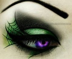 Green and black eye makeup with spider web design.