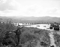 Litter bearers move up as infantrymen of the U.S. 24th division cross foot-bridge over swollen stream on the east central front in Korea on Sept. 15, 1951. Jeeps and trucks are ferrying equipment and men across the stream. (AP Photo/George Sweers)