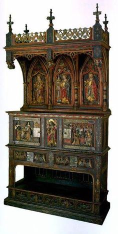 Dresser, Second half of the 15th century, France.    Oak, copper, iron; carved, painted and gilt.    Altered and embellished in the 19th century. Undoubtedly authentic are the carving on the central panel under the cornice showing St Barbara, St Mary Magdalene and St Catherine, and the scenes of the Annunciation and Adoration of the Magi on the cupboard doors, as well as the ornamental carving which combines elements of Gothic and Renaissance patterns.