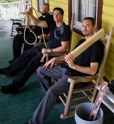The team on the front porch of the Riddle House with the chilling symbols of its ghostly lore