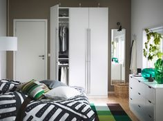 A bedroom with white PAX VINTERBRO wardrobe with stainless steel handles, NORDLI chest and bed in white and a green STOCKHOLM rug.