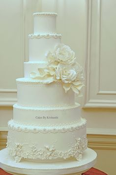 An elegant ivory wedding cake with hand piped details, sugar cherubs and sugar flowers