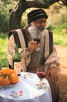 Osho drinking a glass of wine
