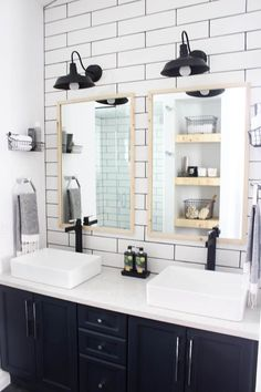 A beautiful modern bathroom renovation with chrome and matte black faucets, sleek modern fixtures and natural wood accents. Beautiful transformation! Subway tile with black grout, wood grain tile, chandelier above tub, matte black faucet, matte black lighting, maroon rug, purple rug, rectangular vessel sinks, natural wood accents, industrial chic, navy cabinets