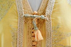 A golden beauty!  This elaborate vintage garment, called a takshita, has 2 pieces.  Covered in a soft metallic embroidery with ornate handmade passementarie buttons and a tassel closure.  This is a beautiful display piece.  I believe this is silk. Most likely from the 1960s or 70s. Available at Maryam Montague's online Souk!