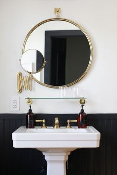 Black and brass bathroom with round mirror and pedestal sink