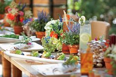 Table set with multiple flower pots and food decorated with flowers and greens