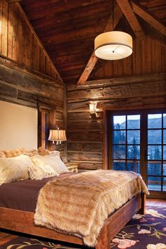 Log skins were adhered to conventional framing to give the master bedroom the look of an old log cabin.