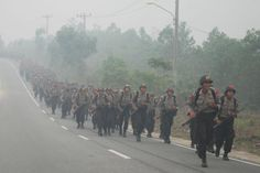 "Students of State Police School (SPN) run amid haze while attending a physical exercise in Pekanbaru, Indonesia Riau province, September 30, 2015 in this picture taken by Antara Foto. Indonesia has sent nearly 21,000 personnel to fight forest fires raging in its northern islands, the disaster management agency said on Tuesday, but smoke cloaks much of the region with pollution readings in the ""very unhealthy"" region in neighbouring Singapore. REUTERS/Rony Muharrman/Antara Foto"