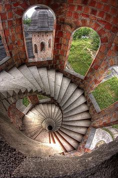 Real life M. C. Escher art- Spiral stairs = math inside Lapalice Castle in Poland. Arched stone windows. Renaissance England style, European gardens world beyond cool & dark stone fortress tower. RESEARCH - http://www.pinterest.com/DianaDeeOsborne/intriguing-architecture/ -  Kartuzy is home to weirdest sight: Polist artist Kazimierczyk got ok in 1979 to build 170 sq/m work studio overlooking lake. Ran out of money. Unfinished Architecture = 5,000 sq/m mock castle w gateways, turrets…