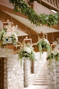 Forget candles — copper lanterns overflowing with a variety of greens add a much more personal stamp to your wedding, especially when hanging from a garland as a whimsical accent.