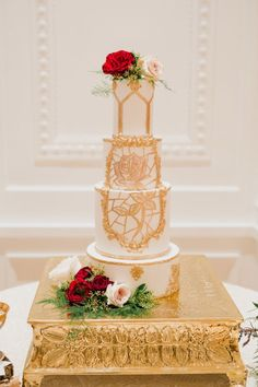 Beauty and the Beast inspired gold and red floral topped wedding cake: http://www.stylemepretty.com/california-weddings/2017/03/17/a-wedding-shoot-inspired-by-beauty-and-the-beast/ Photography: Damaris Mia - http://www.damarismia.com/ Assistant: Dennis Roy Coronel - https://www.dennisroycoronel.com/