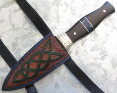 "This custom Sgian Dubh knife features a 4"" dagger point, convex ground, water pattern Damascus blade with traditional spine grooves, hardened to HRC 58. The Sgian Dubh is 9"" overall. The Sgian Dubh has full tang construction for strength, with hammered Nickel Silver bolsters, Tasmanian Blackwood scales, two Nickel Silver pins and an inlaid checkered band of Onyx and Malachite/Azurite, to match the Campbell tartan. Custom leather kilt sheath and Kydex belt sheath included. $672 SOLD"