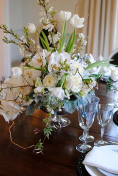 Table centerpiece of white & pale blue hydrangea, ivory garden roses, white french tulips, phaeleanopsis orchids and peach blossoms.