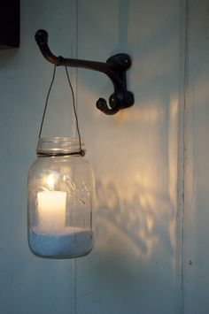 Mason jar votive candle holders at night. Sand and a citronella candles in mason jars hung from plant hangers. For le patio.