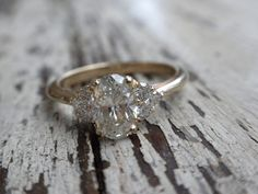 Classic with a twist.  .80ct oval center stone accented with a cluster of three round brilliant diamonds on either side.