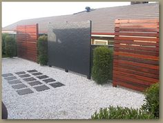 White pebble walkway with dark grey pavers which math the focal point privacy screen. #landscaping