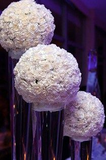 Pomanders of white carnations float in tall vases filled with water.