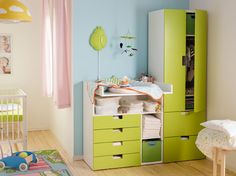 A baby room with STUVA changing table and wardrobe in green and white.