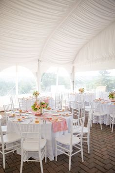 White Linen-Draped tent with white tables and coral accents