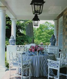 Casual Dining on The Veranda by Carolyne Roehm.  Sunbrella blue & white striped fabric tablecloth is as practical as it is pretty. - The Enchanted Home