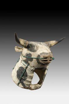 Masque Essenié ou Vaca bruto. Masque casque représentant une tête de taureau sauvage, à la tête massive et au cou épais et puissant que représentent les différents plis, les cornes sont de véritables cornes. On retrouve sur ce masque les dessins de cartes à jouer motifs prisés par les Bijogos. Le mufle est usé par l'usage qu'il est fait du masque, le porteur labourant le sol avec le mufle du masque. Les cordes servent à arrimer