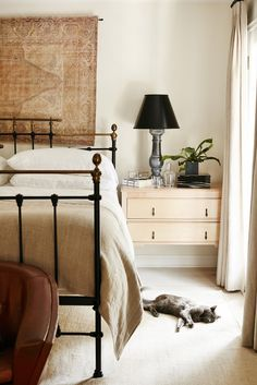 A neutral colored bedroom with a light wood nightstand, metallic and black lamp, wall tapestry and a wrought iron bed.