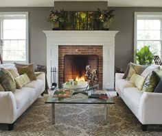 Grey remains the most popular neutral among designers at the moment. Here, Benjamin Moore's Sparrow (AF-720) makes the creamy white fireplace stand out, while summery green accents keep the look seasonal.