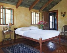 In one of the children's rooms, the rope bed and rugs are vintage, and the walls are plaster. I love the ceiling...