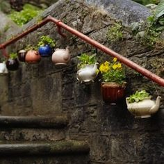 Teapots, Short and Stout ~ Cracked teapot got you down? Look at this charming, cheerful series of teapots adorning the railing of a stone staircase. Any cracks would be perfect for drainage!