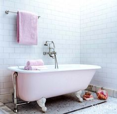 White subway tile in bathroom with pink tub and pink towel