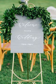 Romantic grey and white wedding welcome sign with greenery garland and vintage gold easel   Lee Calleja Thomas Photography