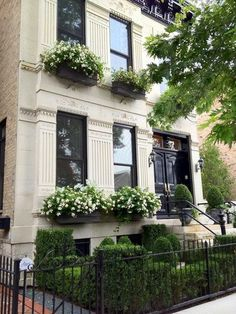 Limestone townhouse with glossy black doors and cornice, complete with green and white window boxes, and an iron gated front garden filled with boxwood hedges in Lincoln Park, Chicago – aka my dream. I will take the whole thing please and thank you. Exterior Design, Interior And Exterior, Exterior Windows, Black Exterior, Black Doors, Black Windows, White Gardens, My Dream Home, Curb Appeal