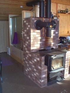 """Hybrid masonry stove   """"We used a style common in Germany, the hybrid masonry stove. It uses a steel or cast iron stove for the firebox but wraps masonry around the metal on 4 or 5 sides, excluding the loading door and, optionally, a cook-top. We added a large masonry chamber behind the stove to allow flue gases to circulate through some extra mass, boosting the total masonry weight to 2 tons."""""""