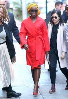 It's a wrap: Lupita covered up in a red, fringed coat when she arrived at the studio  ...