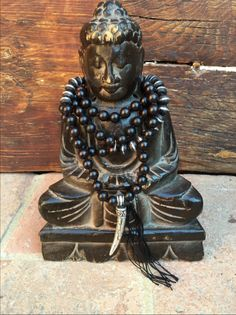 """10mm """"Brunette"""" Boxwood 108 Bead Mala with White Brass Ganesha's Tusk. Hand knotted using 6 strands of black silk. Hand-made 4"""" Silk fringe at end by Ganesha's Tusk. Accent beads on side are Recycled"""