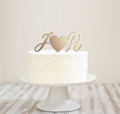 Topo de bolo com duas iniciais maiúsculas e um coração, com dentes para afixar no bolo (acompanha base caso não queira fincar no bolo), Acabamento dourado, 3mm de espessura.Tamanho aprox. 15cm de base x 06cm de alturaMaterial: Acrílico com acabam...